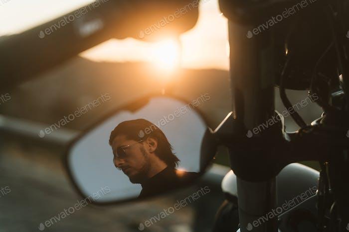 Handsome biker looking away through mirror of his motorcycle