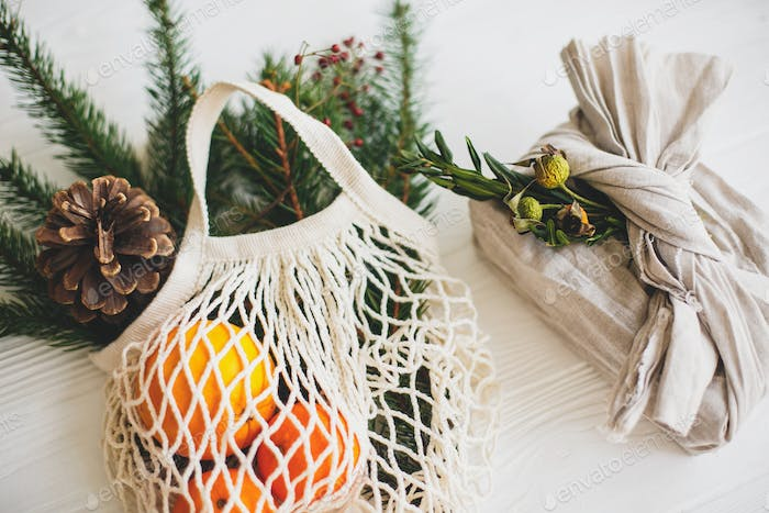 Net cotton bag with green spruce branches, oranges and pine cones