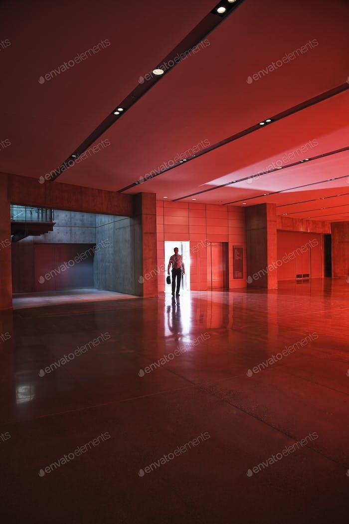 Geschäftsmann geht durch die Tür eines Lobby-Bereichs, der von Tageslicht durch rot getöntes Glas beleuchtet wird.