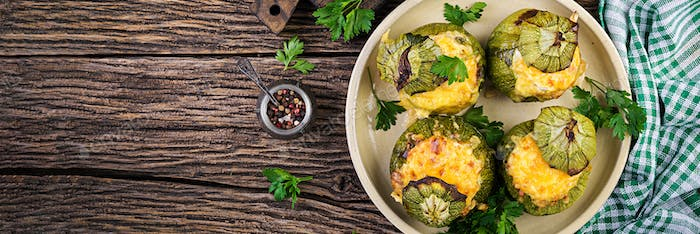 Zucchini stuffed with minced meat, cheese and green herbs. Baked
