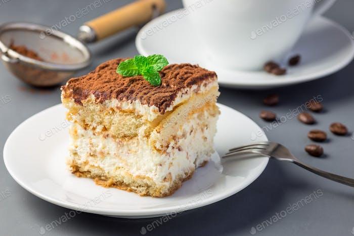 Piece of traditional italian Tiramisu dessert cake on white plat
