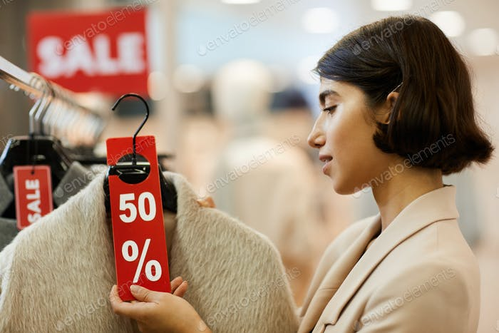 Young Woman Choosing Clothes on Sale
