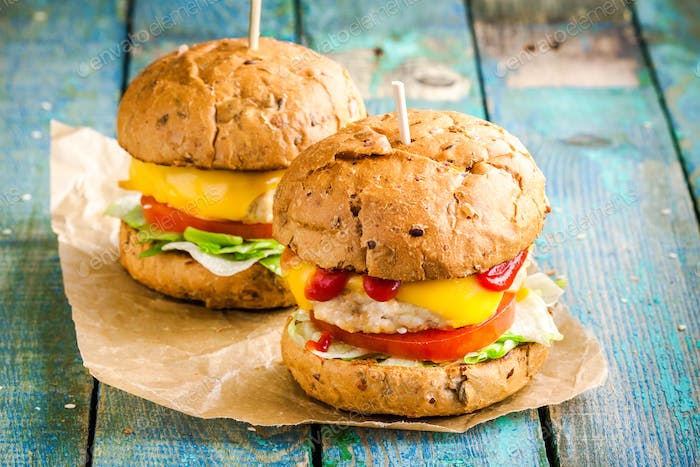 two home burgers with fresh vegetables and chicken cutlets on paper