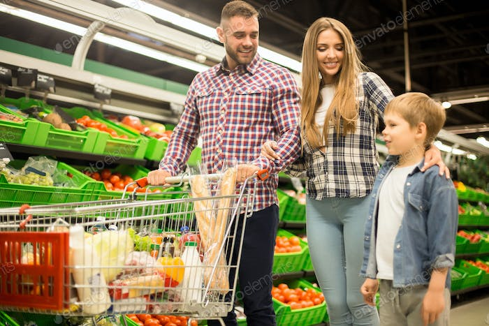 Happy Family Shopping for Groceries in Supermarket