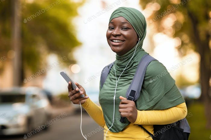 Cheerful African Muslim Lady In Hijab Holding Smartphone, Listening Music Outdoors