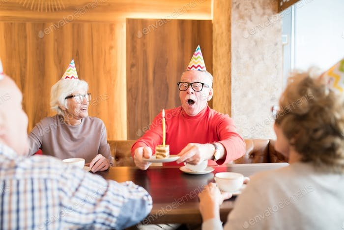 Excited elderly man blowing out cake candle