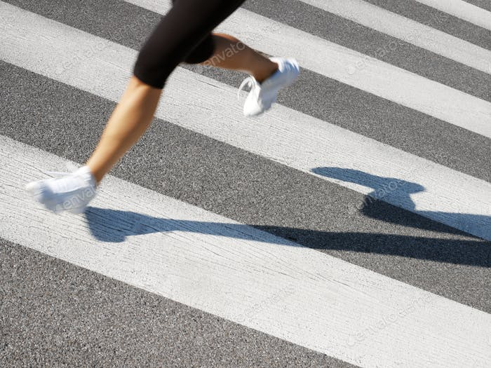 Female Runner Crossing Street On Zebra Stripes