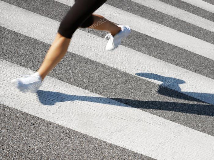 Female Läufer Crossing Straße auf Zebra Streifen