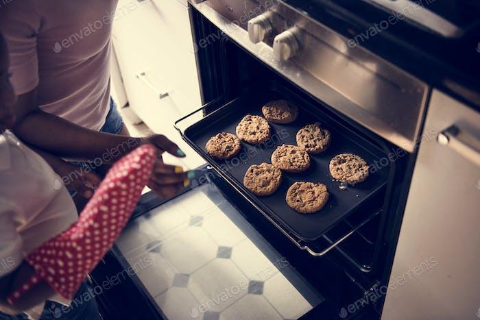 schwarz Kind helfen Mama Backen Cookies in die Küche