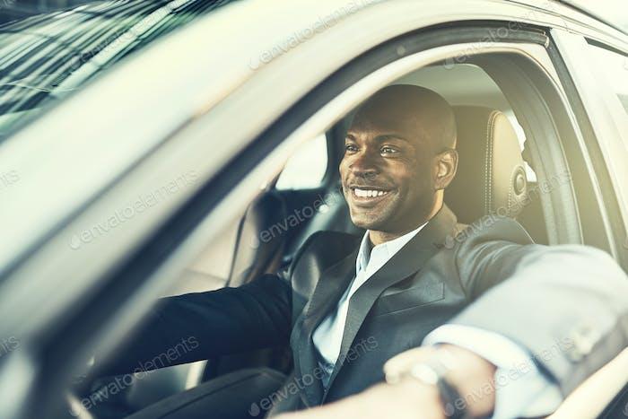 Afrikanischer Geschäftsmann lächelnd beim Autofahren seines Autos in der Stadt