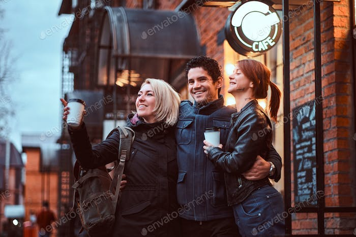 Cheerful friends standing together in an embrace near a cafe outside, looking away.