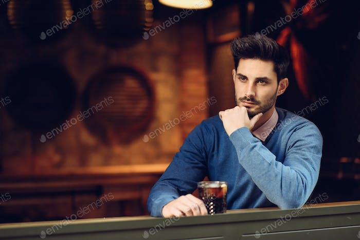 Pensive guy with modern hairstyle near a window drinking a soda.