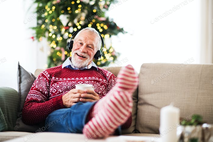 A senior man with headphones listening to music at home at Christmas time.