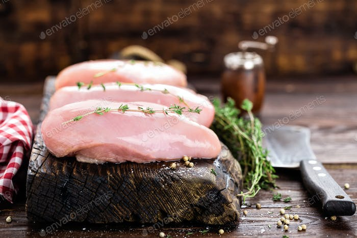 Raw chicken meat fillet on wooden background top view