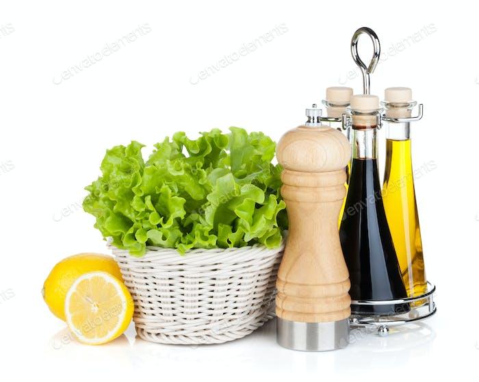 Salat im Korb mit Zitronenfrüchten, Pfefferstreuer, Olivenöl und
