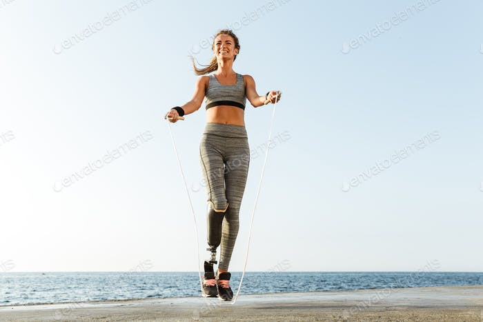 Disabled sports woman jumping with skipping rope