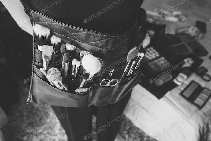 Maquillador profesional con bolsa de cinturón con Pinceles de maquillaje.