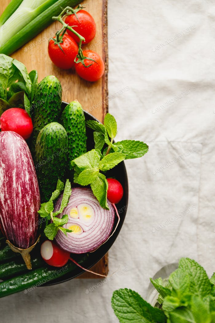Fresh colorful vegetables for making summer salad in a plate, copy space.