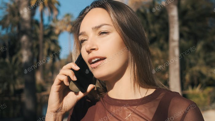 Attractive girl arguing with friend during talk on phone in park