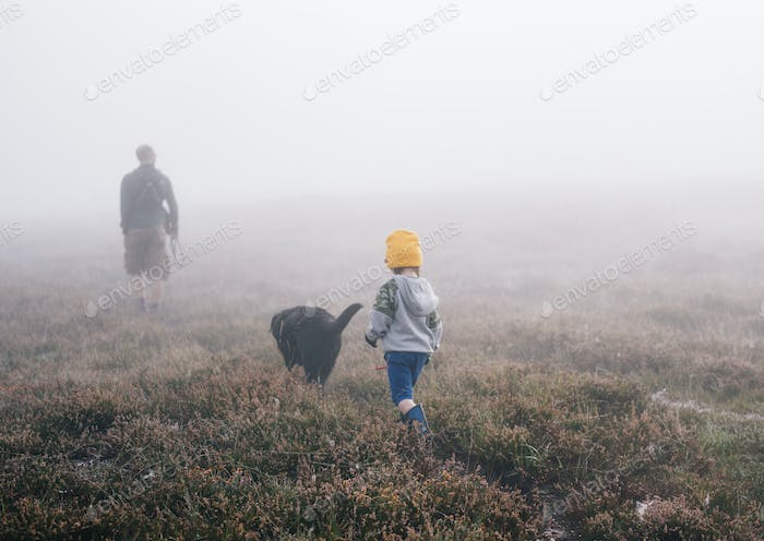 An adult and a child with a dog, walking through heather in autumn mist.