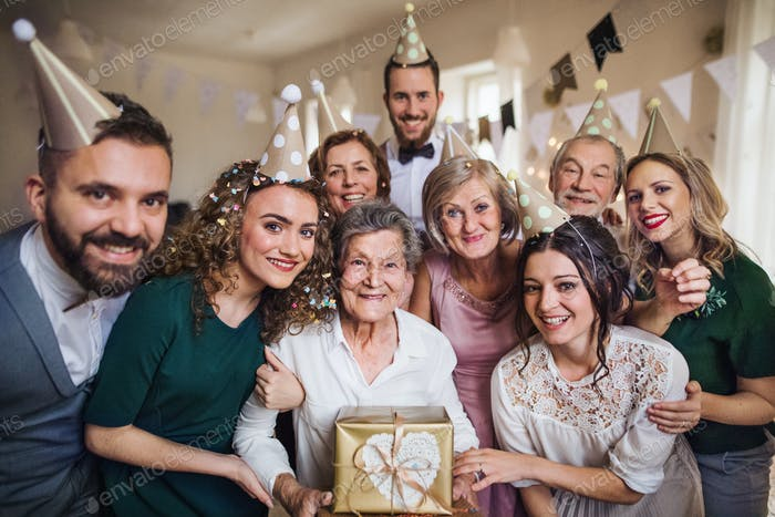 A portrait of multigeneration family with presents on a indoor birthday party.