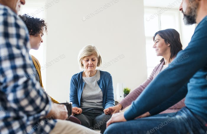 Men and women sitting in a circle and holding hands during group therapy.