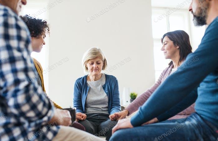 Мужчины и женщины сидят в кругу и держатся за руки во время групповой терапии.