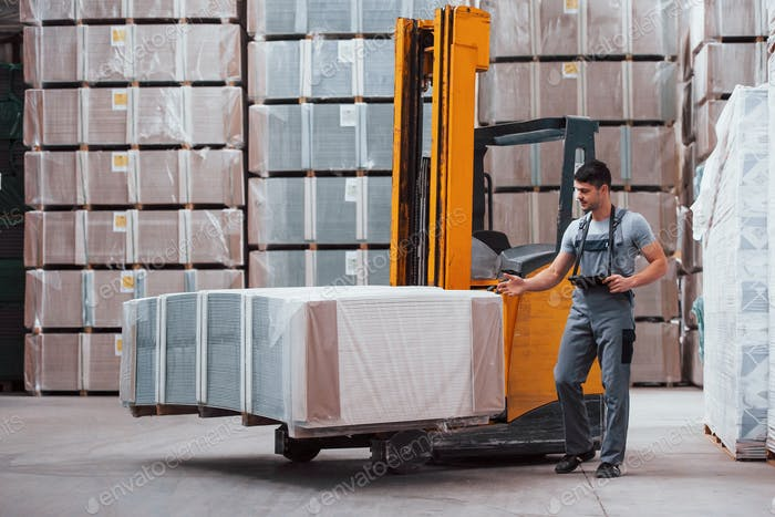 Portrait of young worker in unifrorm that is in warehouse near forklift