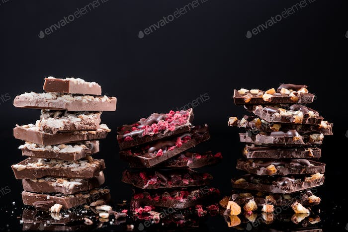 Stack of Broken Chocolate Pieces on Black Background. Copy Space. Closeup View