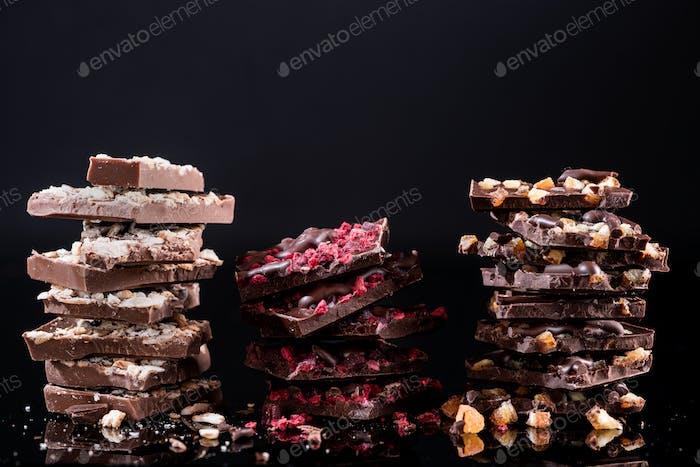 Stapel von zerbrochenen Schokoladenstücken auf schwarzem Hintergrund. Leerzeichen kopieren. Nahansicht