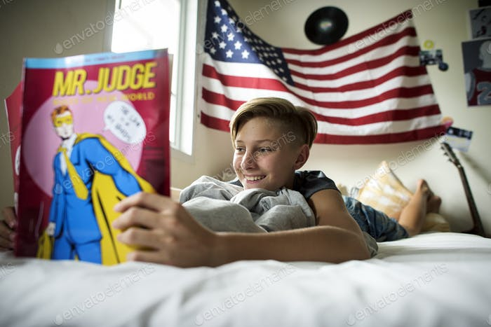 Young caucasian boy lying reading cartoon on bed