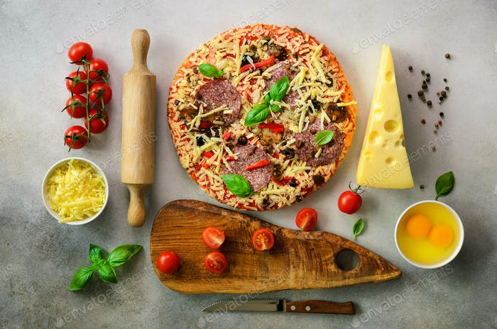 Food ingredients for italian pizza, cherry tomatoes, flour, cheese, basil, rolling pin, board, knife
