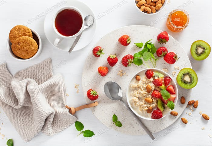 gesundes Frühstück mit Haferbrei, Erdbeere, Nüsse, Marmelade und