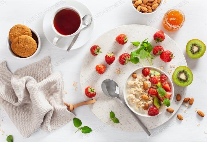 healthy breakfast with oatmeal porridge, strawberry, nuts, jam a