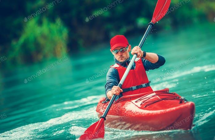 Paddling Kayaker on the Scenic Lake