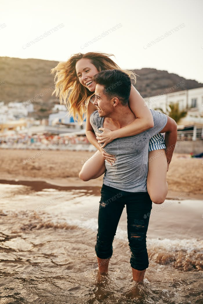 Young man carrying his laughing girlfriend into the ocean surf
