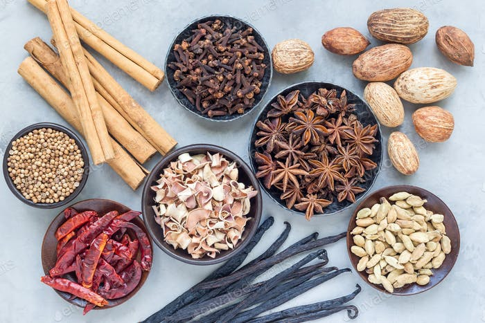 Aromatic winter spices in bowls and on background, top view, horizontal
