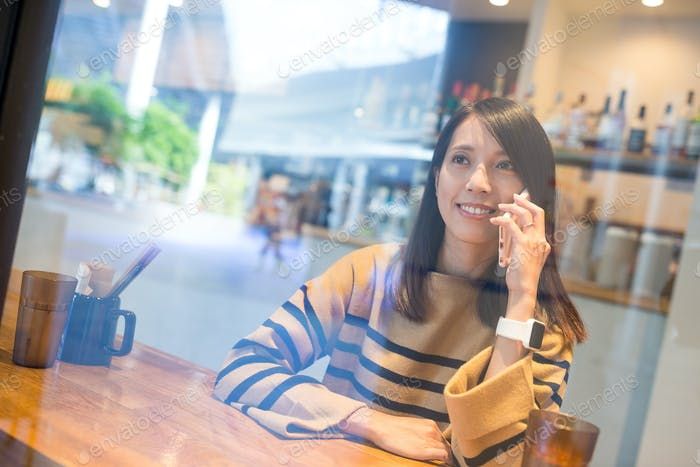 Woman talk to mobile phone in restaurant