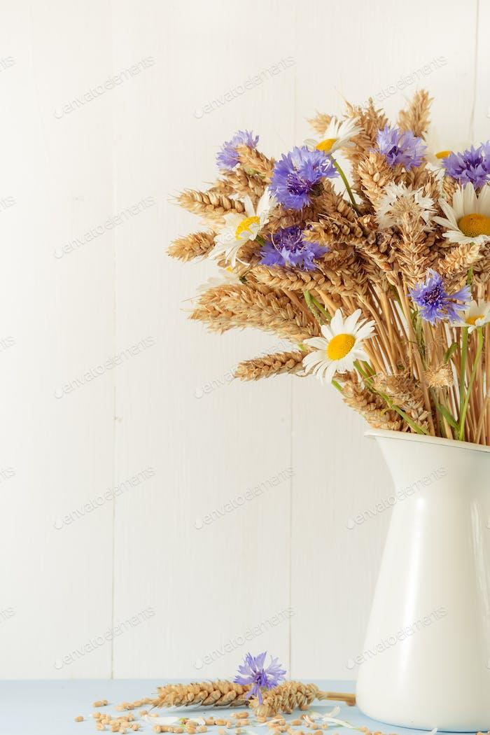 Reifer Weizen in weißer Vase auf hölzernem Hintergrund