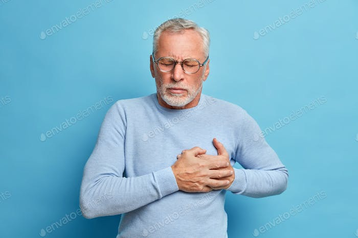 Senior man in spectacles presses hand to chest has heart attack suffers from unbearable pain closes