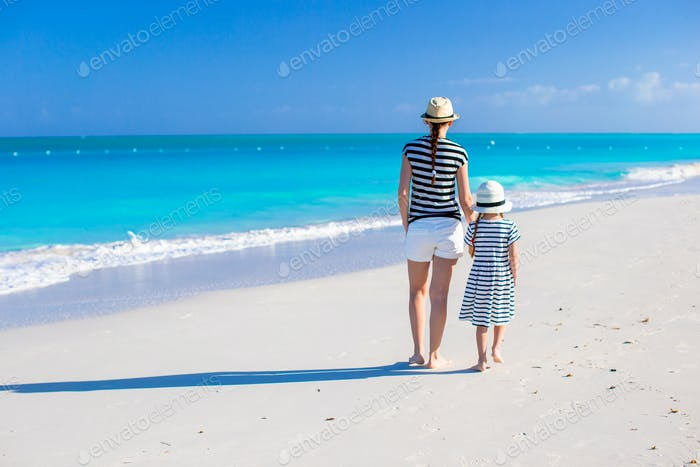 Back view of young mother and little daughter at caribbean beach