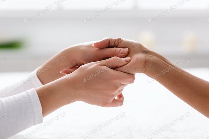 Physiotherapeut drückt spezifische Flecken auf der weiblichen Handfläche