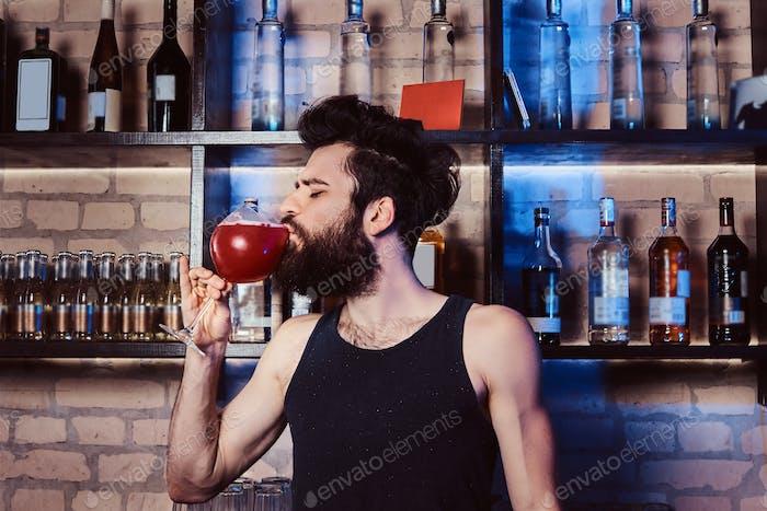 Престижный бородатый бармен пьет бокал с коктейлем Aperol spritz за барной стойкой