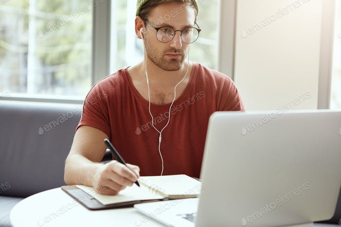 Hardworking young bearded man wearing hat and glasses studying via Internet, listening to business w