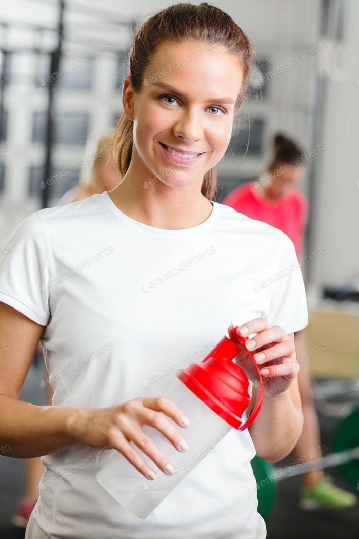 Smiling woman in workout outfit holding a drinking bottle at fitness gym