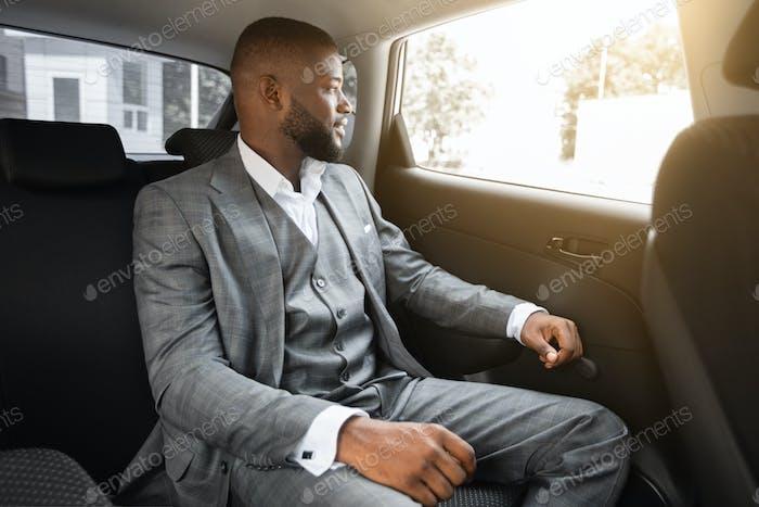 Elegant african american businessman looking through car window