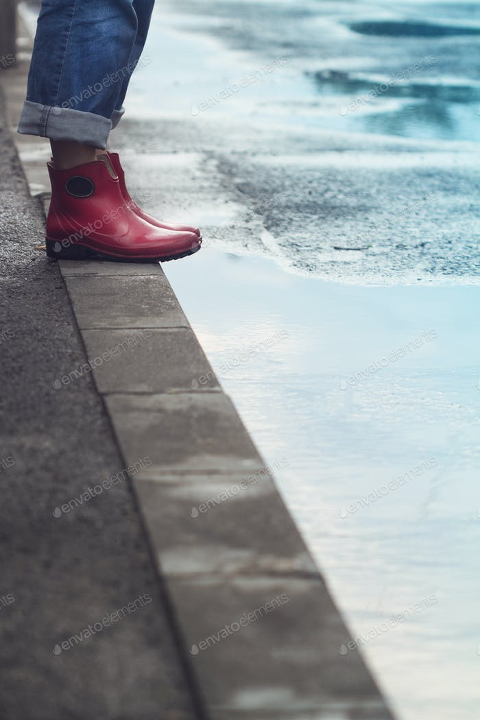 woman with red short boots standing on sidewalk next to a puddle