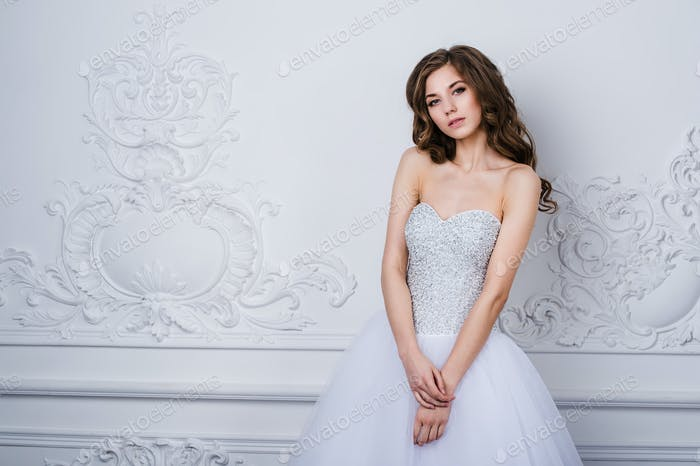 Beautiful smiling bride woman with long curly hair posing in wedding dress at interior. Beauty