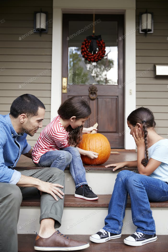 Father And Daughters Drawing Face On Halloween Pumpkin