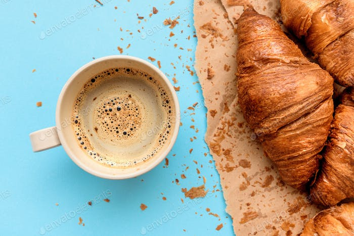 Coffee and croissant for breakfast, top view